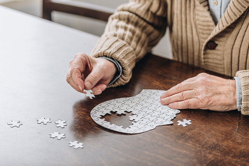 Older man putting together puzzle shaped as human head