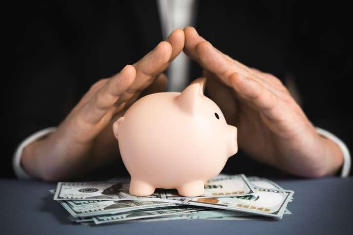 Money Protecting concept. Saving symbol - Close-up Of A Human Hand Protecting Pink Piggy Bank