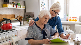 Mature woman helping elderly mother with paperwork