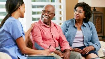 Nurse and senior couple talking at a home visit