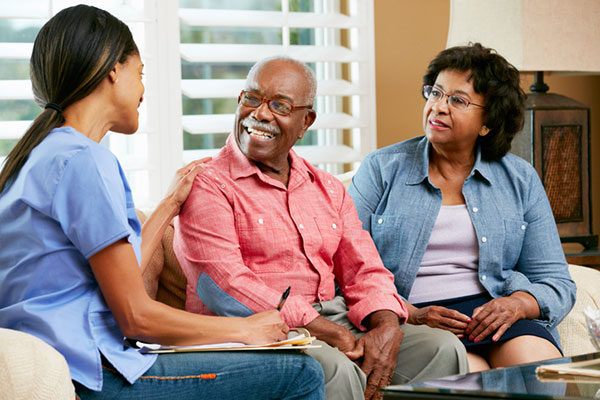 Nurse and senior couple talking at a home visit