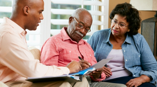 Estate Planning Attorney Talking To Senior Couple At Home