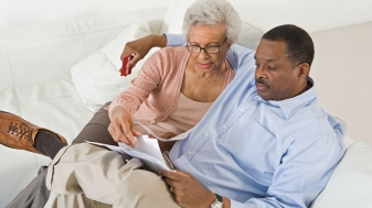 Older couple sitting on couch looking over their estate plan