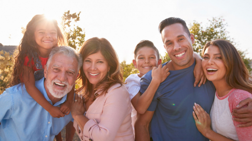 Portrait Of Multi-Generation Hispanic Family Relaxing In Garden At Home Together