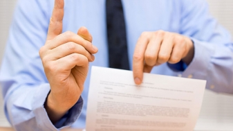 Man holding paper and holding up one finger