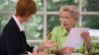 Adult woman and senior woman looking over paperwork for edicaid Crisis Planning